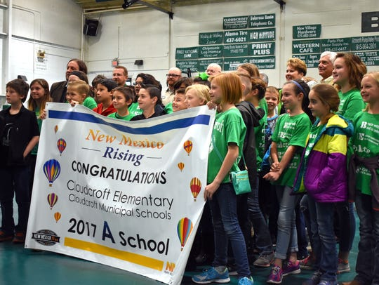 Students from Cloudcroft Elementary hold up their new