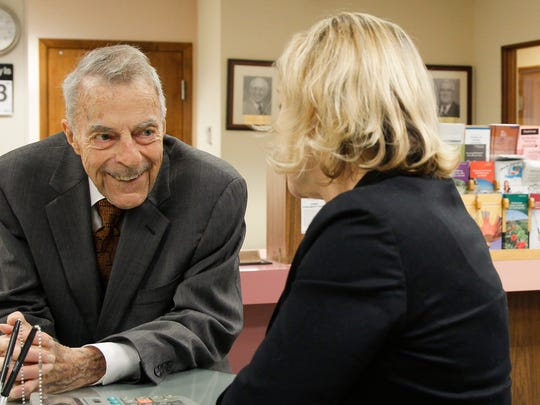 Rollie Dart, 89, Chairman Emeritus and Community Relations Officer of Dart National Bank chats it up with Executive V.P. and Marketing and Advertising Director Sally Rae,  October 13, 2015, at the main branch in downtown Mason.  He served as chairman from 1962-2005.  [MATTHEW DAE SMITH | for the Lansing State Journal]