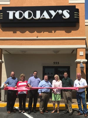 Alan Nuckles (from left), TooJay's senior vice president of Operations, Purchasing & Construction; Cheryl Neenan, area director; Brett Carper, director of operations; Chris Artinian, President and CEO; Vero Beach Mayor Laura Moss; Bryan McDaniel, TooJay's general manager; and Vero Beach County Commissioner Peter O'Bryan attend the ribbon cutting for its newly remodeled Vero Beach restaurant.