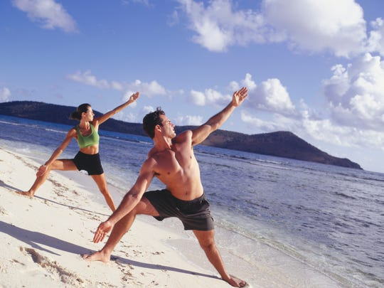 Man and woman doing yoga on beach