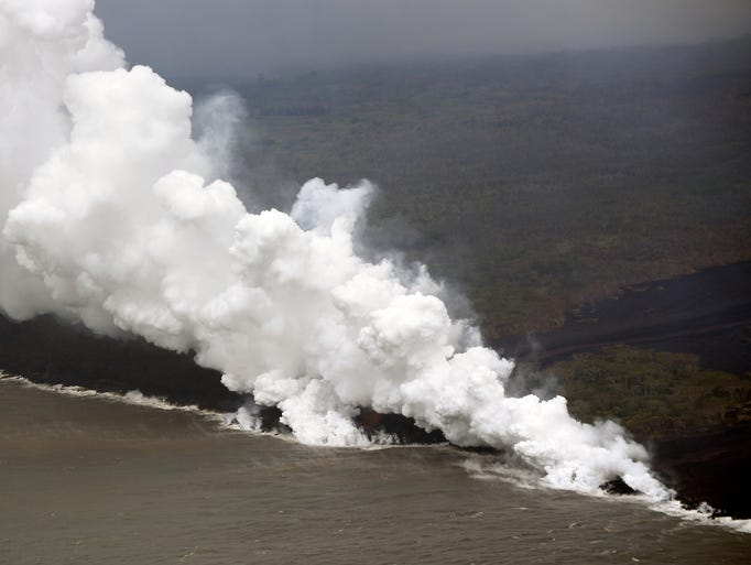 Steam and smoke billow from the lava flow running into