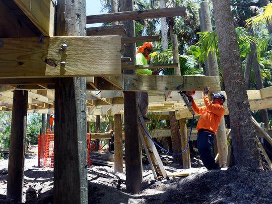 Cirilo Gomez (left) and Juan Gomez, of Big Cypress Tiki Huts, work on installing planking and boards along an elevated boardwalk in June at the Children's Garden at McKee Botanical Garden in Vero Beach .
