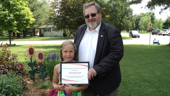 Cassidy Kodl was awarded a $200 scholarship from Catholic Financial Life for the 2016-2017 school year. Cassidy is the daughter of Christopher and Tara Kodl, and is in the third grade at Thorp Catholic School. Presenting her with a scholarship certificate is Thad Streeter, Catholic Financial Life advisor in Wausau.