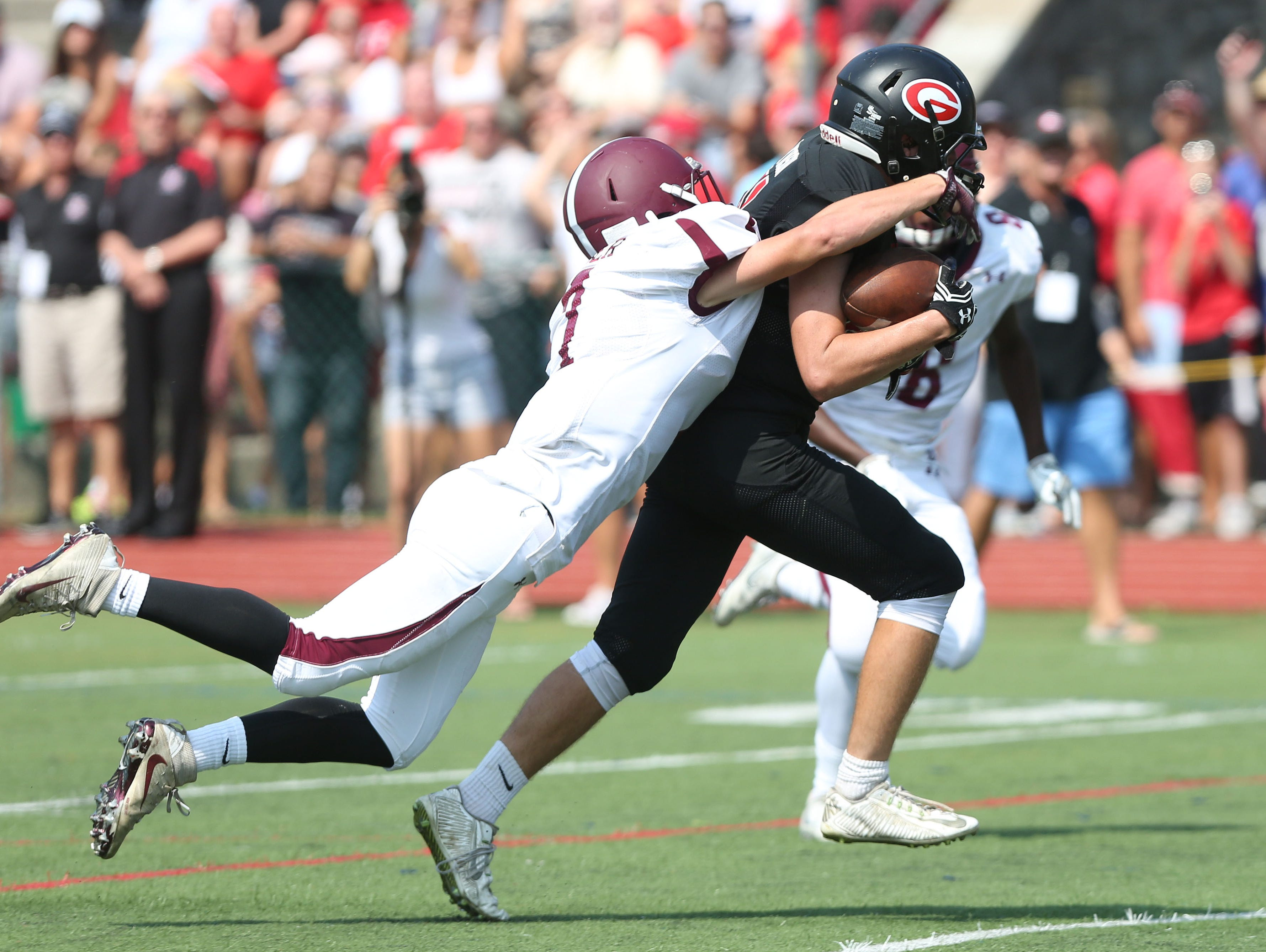 Rye's Will Hynson drags Harrison's Brett Silber into the end zone after catching a pass from T.J. Lavelle during first half of the teams' annual rivalry game at Nugent Stadium at Rye High School on Saturday. Rye won the game 42-12.