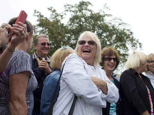 Janet Schuch, of New Baltimore, reacts after a newspaper with a photograph of her was removed from the time capsule Friday at Central Middle School in Port Huron.