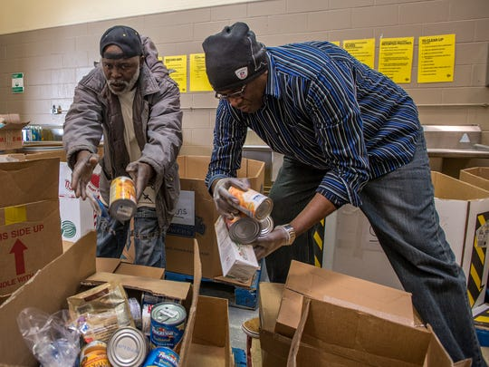 Maryland Food Bank volunteers Levi Brown of Pocomoke and Telal Amed of Salisbury sort food.