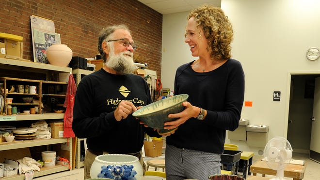 Brian McCarthy (L), cofounder of Odyssey Center for Ceramic Arts, and Becky Upham, communications manager for MANNA Food Bank, with some of the 1,000 bowls Odyssey artist made for the annual MANNA Empty Bowls fundraiser. The Empty Bowls luncheon is Monday, September 15, at the Doubletree Hotel in Biltmore.