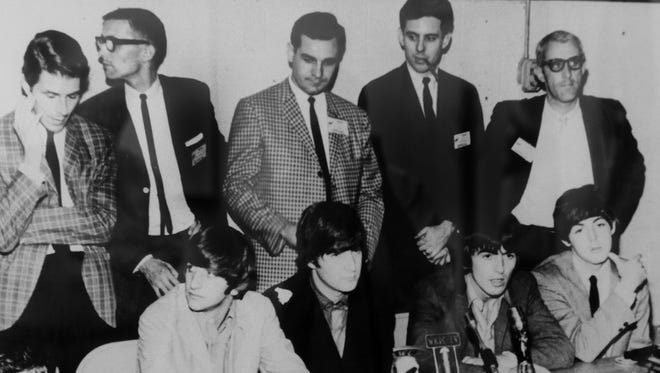 Hamilton County Auditor Dusty Rhodes was one of the WSAI-AM DJs in 1964 who invited the Beatles to play at Cincinnati Gardens that year. This large photo from a press conference hangs in his conference room in the county administration building.  Dusty Rhodes is top row second from right with the pipe, with the Beatles seated, from left, Ringo Starr, John Lennon, George Harrison, and Paul McCartney.