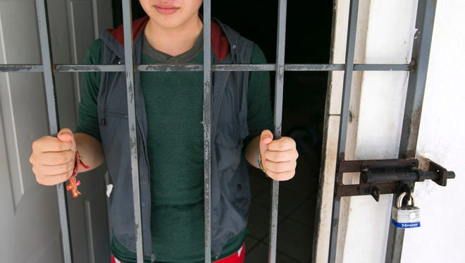 Levi Miranda, 16, of El Salvador, looks out from the locked door of the boys sleeping area on June 19, 2014, at the Instito Nacional del Migracion, a municipal shelter in Reynosa, Mexico. Levi was apprehended by Mexican Federal Police while trying to cross into the United States and brought to the shelter that is receiving growing numbers of Central American children. Levi will be deported back to El Salvador.