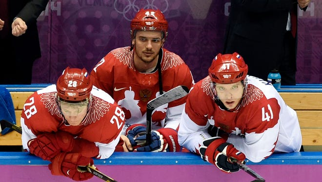 Russia forward Alexander Syomin (28) , forward Nikolai Kulyomin (41) and forward Artyom Anisimov (42) react on the bench after losing to Finland in the men's ice hockey quarterfinals during the Sochi 2014 Olympic Winter Games at Bolshoy Ice Dome.
