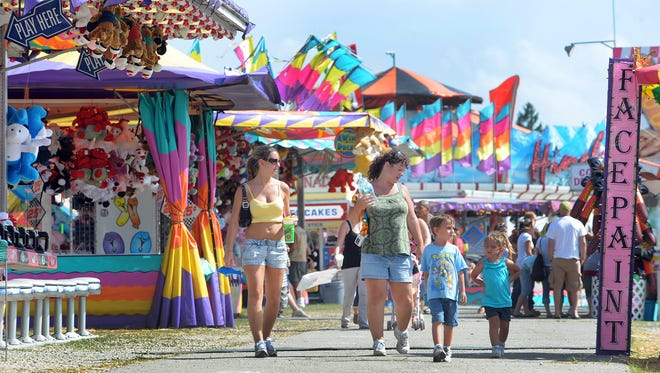 Families roam the sites and sounds of the midway at the Marion County Fair.