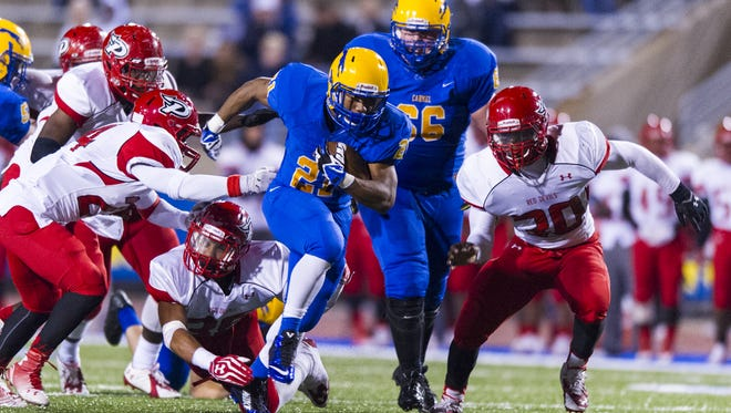 Carmel High School senior Chris Perkins (21) breaks through the Pike defense and heads toward the end zone to score during the second half of action. Carmel High School hosted Pike High School in varsity football action, Friday, September 12, 2014. Carmel defeated Pike 48-21.