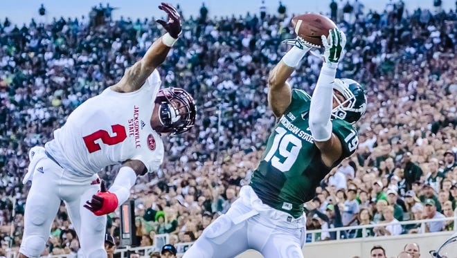 AJ Troup (19) of MSU grabs a pass in the endzone for a touchdown over Jermaine Hough (2) of Jacksonville State late in the 1st quarter of their game Friday August 29, 2014 in East Lansing.  KEVIN W. FOWLER PHOTO