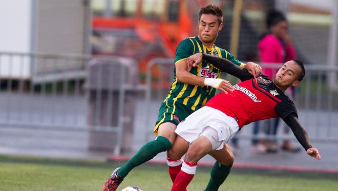 Rhinos' Alec Sandly fights for the ball against Charleston Battery's Adam Mena.