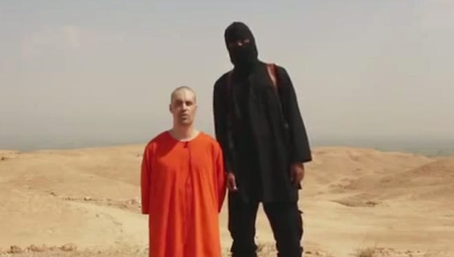 This image shows a frame from a video released by Islamic State militants on Aug. 19, 2014, that shows the killing of journalist James Foley by a militant who spoke with a British accent.