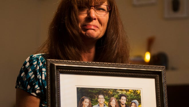 Susan Hunt holding a photo of her family, including her son, Darrien Hunt, at her home in Saratoga Springs, Utah. Darrien Hunt  was killed by police Wednesday. Susan Hunt has criticized police in the Utah County city of Saratoga Springs over the fatal shooting of her 22-year-old son, saying she believes the outcome would have been different had he not been black.