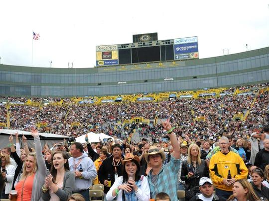 Fans cheer as Billy Currington performs at Lambeau Field.