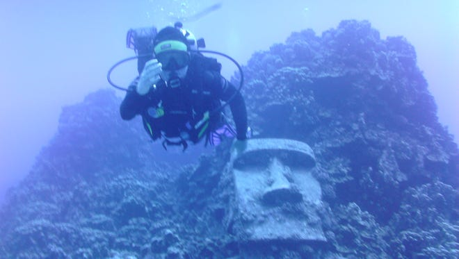 Tracy Hare of Phoenix scuba diving off Rapa Nui with a Moai statue in the background. It is not an original; it had been created for a movie shoot.