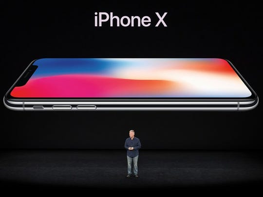 Apple's Phil Schiller standing on stage in front of a screen showing a very large iPhone X.