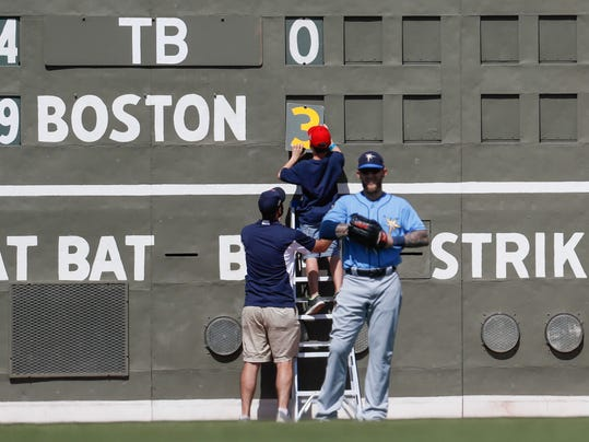 Grounds workers change the scoreboard beside Tampa Bay Rays left fielder Brandon Snyder, right, after Boston Red Sox's Brock Holt hits an RBI double to left field in the first inning of a spring training baseball game, Saturday, Feb. 24, 2018, in Fort Myers, Fla. (AP Photo/John Minchillo)