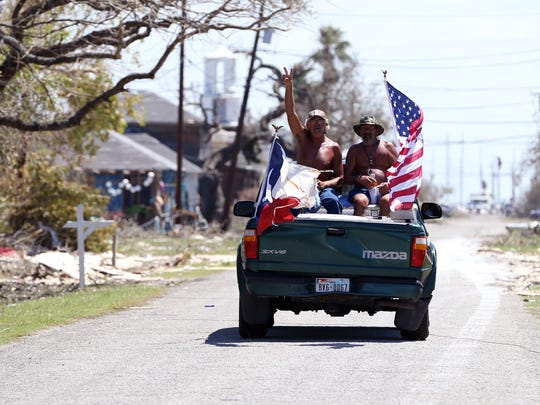 With flags flying from the back of their truck, men survey the damage in Rockport, TX on Tuesday, August 29, 2017, following Hurricane Harvey.