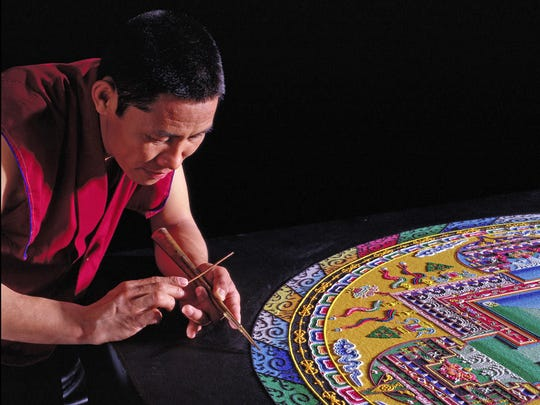 A monk from the Drepung Loseling Monastery creates a sand mandala to help purify the earth and inhabitants.