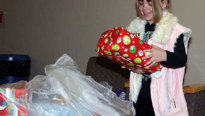 Sara Kirkpatrick checks out the gifts in the bag that her family received during the Windsor Optimist Club's annual toy giveaway in this file photo.