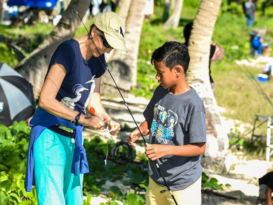 Suzanne Medina helps to bait a hook for her son, Ska