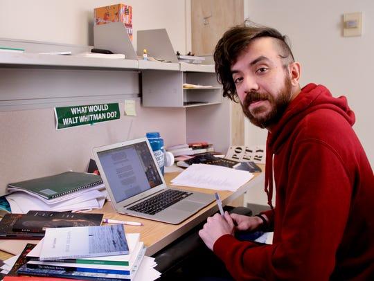 Kaveh Akbar sits at his desk.