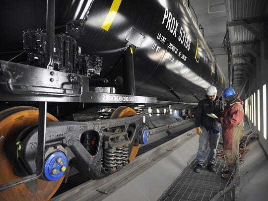 Dan Triggs, left, coatings supervisor, and Clifford Blue, grit blaster, discuss in 2015, a work order on a railroad tank car at Eagle Railcar Services. The company repairs, services and paints rail cars of all types and is expanding their business a third time in Wichita Falls.