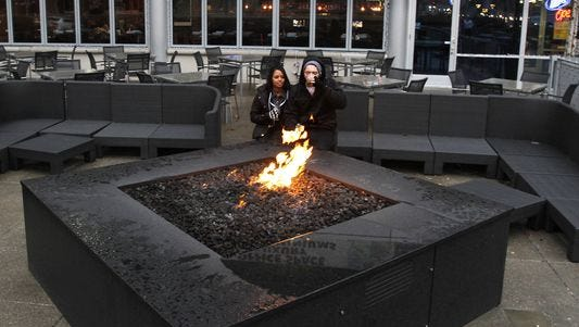 Hosanna Webb and Aaron Hubbard, both Indianapolis, brave the elements as they have a drink and warm themselves by the fire pit in front of Scotty's Brewhouse in Downtown Indianapolison Nov. 21, 2011. Owner Scott Wise said he now plans to expand the chain outside of Indiana with new locations planned in Illinois and Florida.