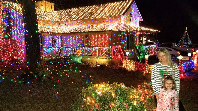 Katie Williams and her daughter Myra Kate visit the light display at 7289 Old Cox Pike in Fairview. The display has been a repeat winner of Fairview's annual Christmas Lights Tour Contest.