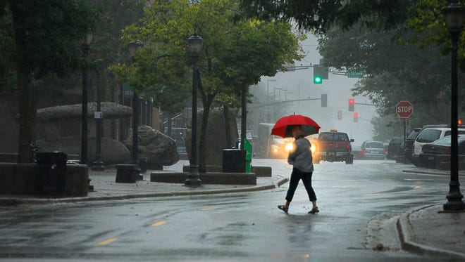 A pedestrian on West St. German Street broke out her umbrellas to contend with the wind and showers in September 2014.