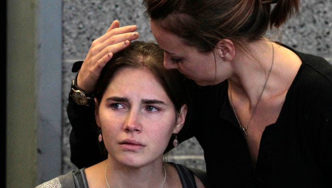 On Oct. 4, 2011, Amanda Knox, left, is comforted by her sister, Deanna Knox, during a news conference shortly after her arrival at Seattle-Tacoma International Airport