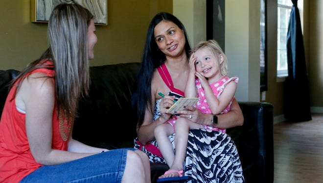 Marie Maher explains bedtime and other daily routines to Lauren Neifert, left, who is sitting for her daughter Luella and son Yves, who is on the autism spectrum. Maher runs a website that links parents of special-needs children with would-be sitters.