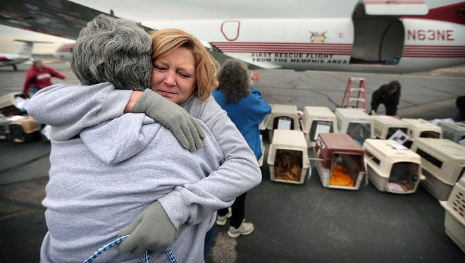 Terri Esther embraces fellow Southern Friends Animal Society volunteer Tammy Wilcox (left) as they drop off dogs at the Memphis airport during a Wings of Rescue airlift for some 100 at-risk shelter dogs. Animal shelters from across the Mid-South brought animals to be flown to Pacific Northwest, where they can be more easily adopted.