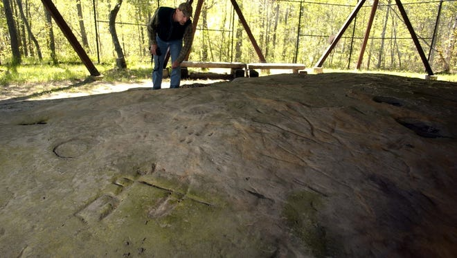 A hunter with a bow and arrow, foreground, is shown carved at the Sanilac Petroglyphs in Greenleaf Township.