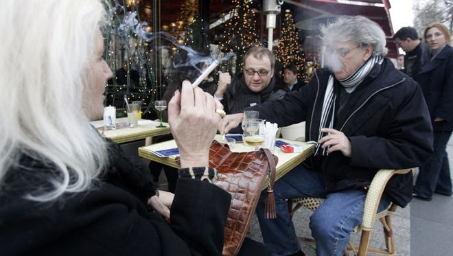 Tourists enjoy a cigarette at a cafe-restaurant on the Champs Elysees in Paris, Jan. 1, 2008.