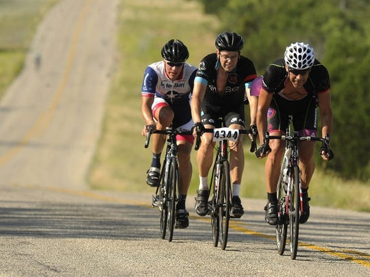 Thomas Metthe/Reporter-News Riders in the 56-mile race cruise down a hill on FM 1086, west of Bradshaw, during the 2015 Tour de Gap.