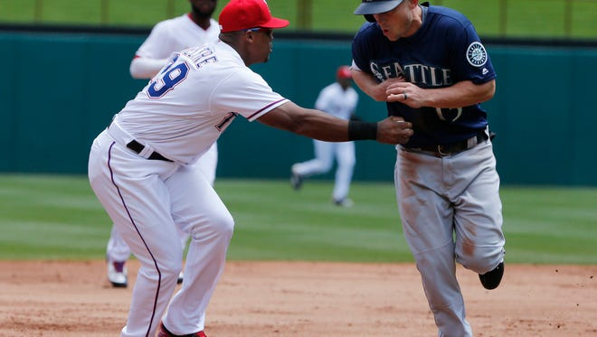Texas Rangers third baseman Adrian Beltre (29) tags out Seattle's Kyle Seager, right, to end the second inning.