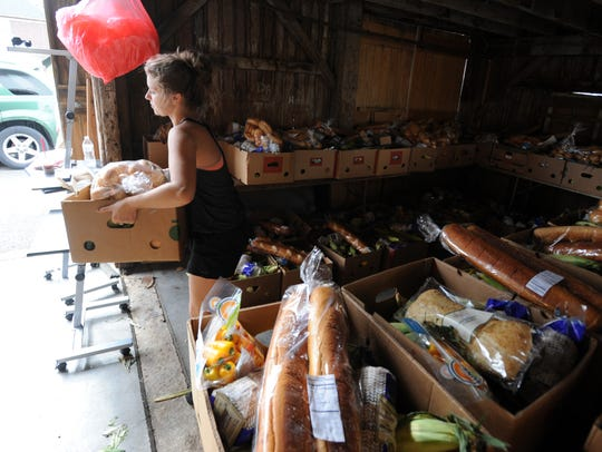 Faith Hankison carries a box of food from a storage