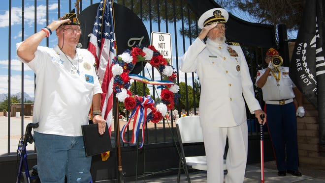 American Legion Post 10 chaplain Lawrence Orvis, left, and retired Navy Capt. Walt Baker stand at attention and salute Sunday as Raymond Rivera plays Taps.