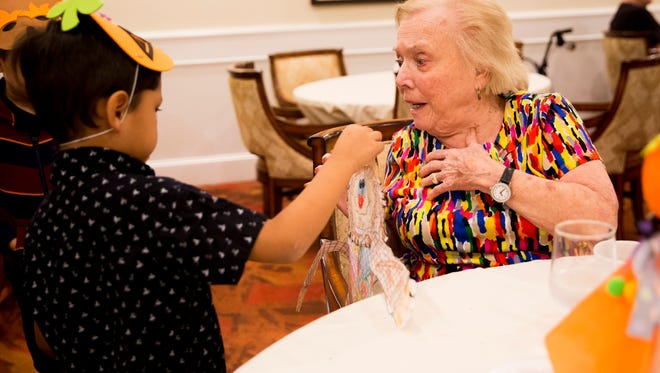 """Jayce Rodriguez, 6, a first-grader at Sabal Palm Elementary, hands his handmade scarecrow to Lee Swenson while she dines at The Carlisle Naples Wednesday, Oct. 25, 2017 in Naples. Swenson, a resident of The Carlisle for nearly 5 years, has received gifts in the past from young students. """"They're just so precious,"""" she said. """"They are so cute."""""""