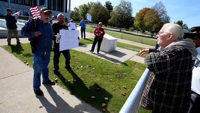 "Separated by a metal barricade, advocates of the open carrying of guns and against ""radical Islam"" yell back and forth with counter protesters on the front lawn of the Henry Ford Centennial Library in Dearborn on Sat., Oct. 10, 2015."