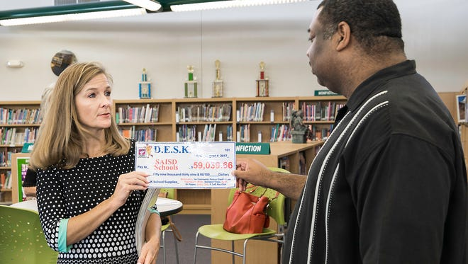 Diane Wilson of the D.E.S.K. organization presents Derrick Jackson, director of communications for San Angelo ISD, a check for $59,040 to purchase school supplies for students Aug. 4 at Glenn Middle School.