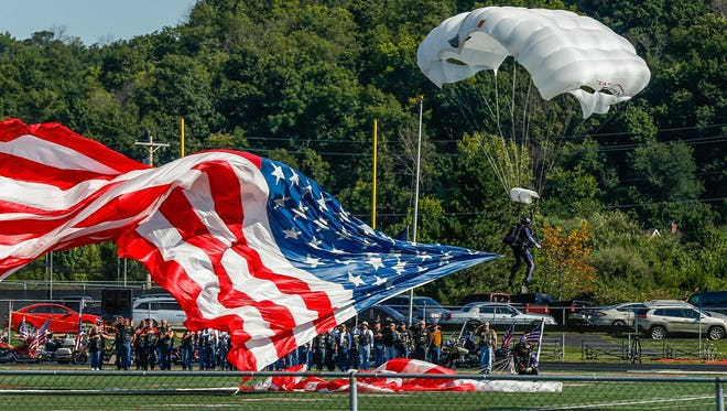 A parachuter lands on the Lakota West football field in West Chester Saturday morning during the funeral service for Army Master Sgt. Corey Hood. Hood, 32, a Lakota West graduate and member of the Army's Golden Knights parachute team, died Aug. 16 following a performance at the Chicago Air and Water Show.