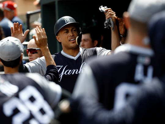 Giancarlo Stanton high-fives teammates in the dugout after scoring on Miguel Andujar's fielder's choice groundout in the first inning against the Baltimore Orioles on Aug. 25.