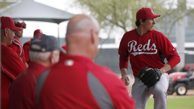 Reds pitcher Homer Bailey throws during his second bullpen session of spring training under the watchful eyes of general manager Walt Jocketty and head athletic trainer Paul Lessard,