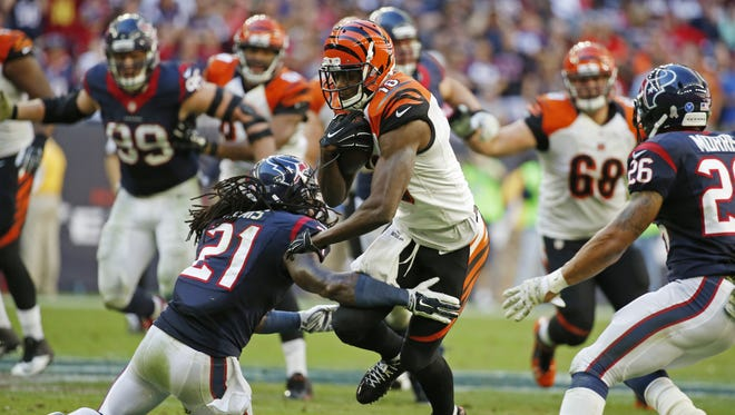 Bengals wide receiver A.J. Green runs through the tackle of Texans free safety Kendrick Lewis after a reception in the second half.