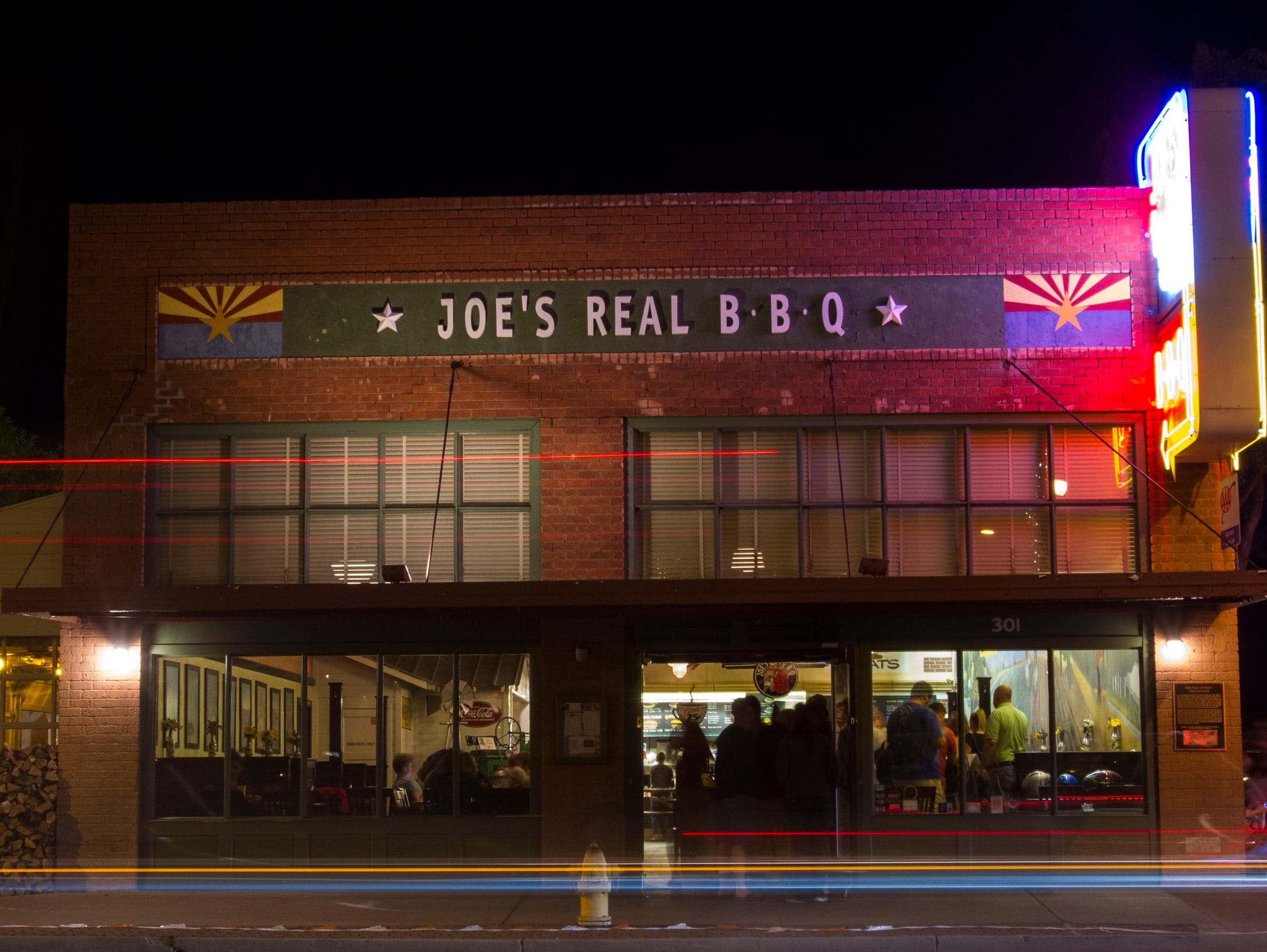 Customers wait in line at Joe's Real BBQ in the Heritage